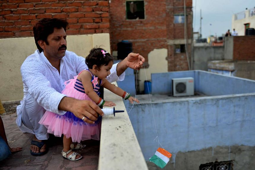 An Indian father and daughter fly kites from their rooftop during celebrations for the country's Independence Day on Aug 15, 2014.