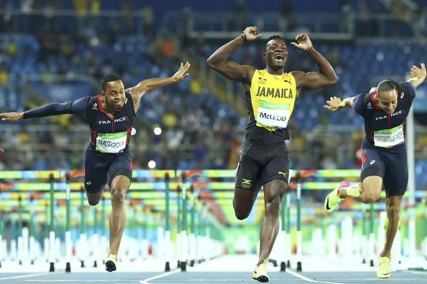 Omar McLeod of Jamaica (centre) crosses the finish line to win the gold, ahead of bronze medallist Dimitri Bascou of France (left) and Pascal Martinot-Lagarde of France (right).