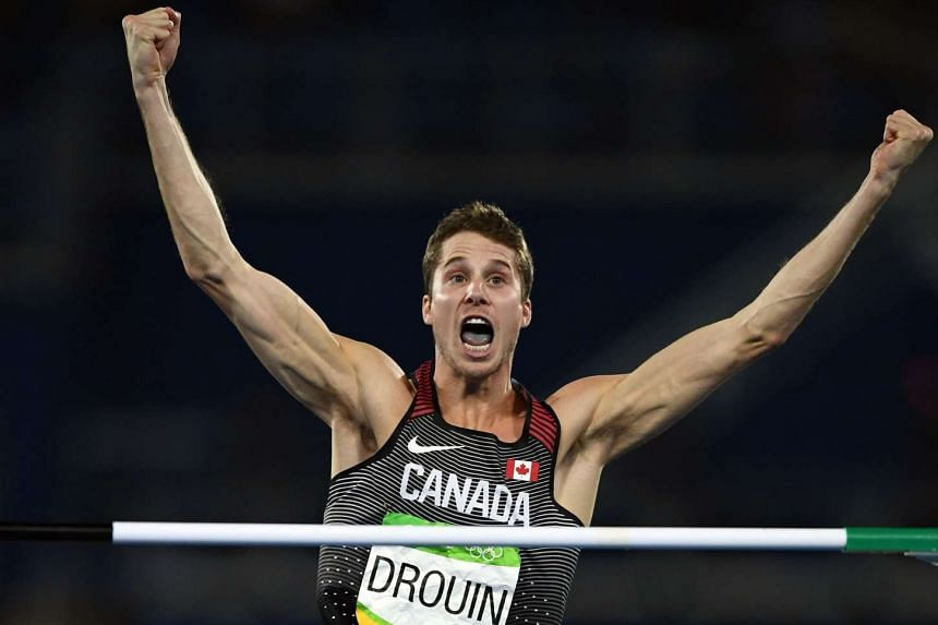 Canada's Derek Drouin celebrates after clearing a jump.