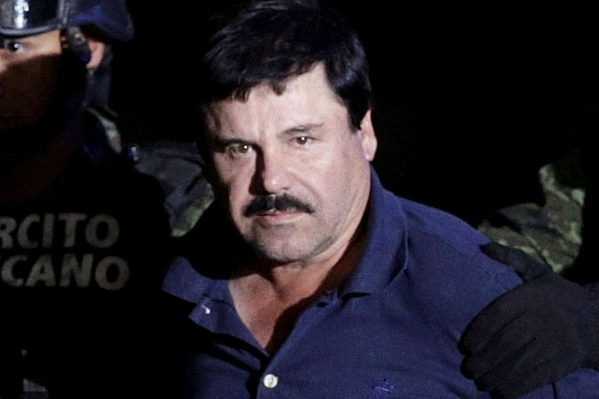 """Recaptured drug lord Joaquin """"El Chapo"""" Guzman is escorted by soldiers at the hangar belonging to the office of the Attorney General in Mexico City, Mexico on Jan 8, 2016."""