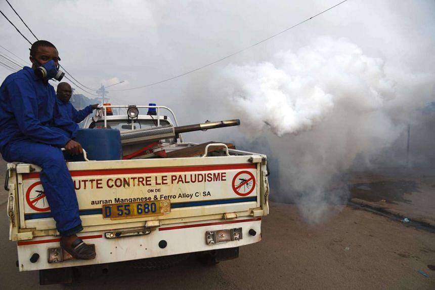 A team from the National Institute of Public Health sprays anti mosquito product through the Koumassi district of Abidjan on August 15 during an operation aimed at preventing the spread of the Zika virus.