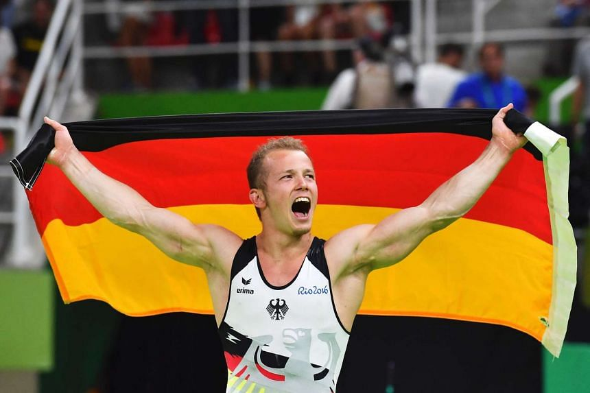 Germany's Fabian Hambuechen celebrates after the men's horizontal bar event final.