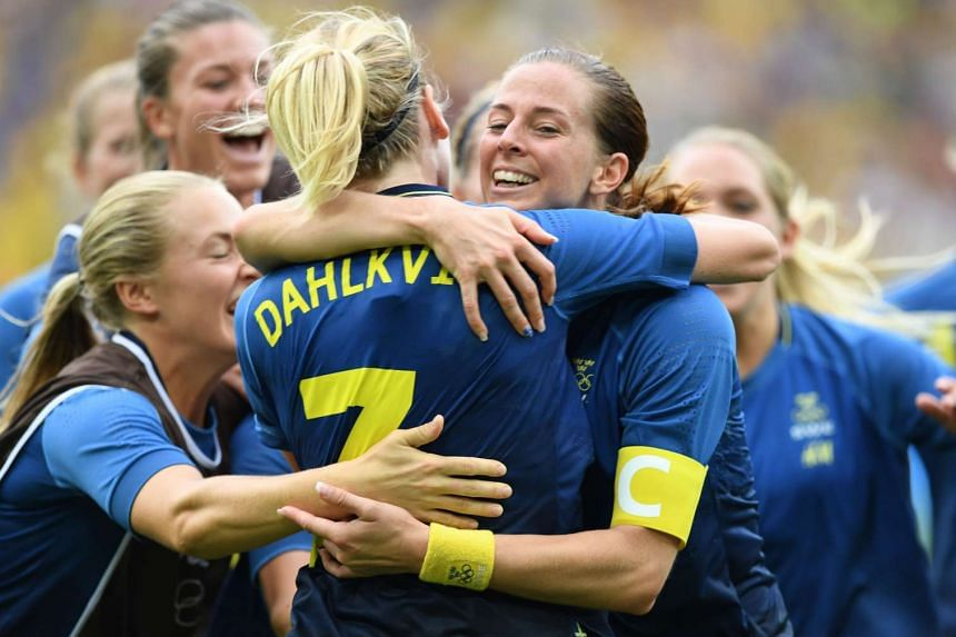 Swedish players congratulate Swedish striker Lisa Dahlkvist after her winning penalty.