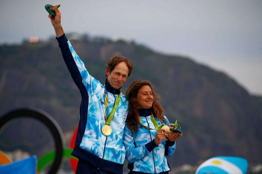 Santiago Lange (left) and Cecilia Carranza Saroli of Argentina react to receiving the gold during the awards ceremony in the Nacra 17 Mixed class of the Rio 2016 Olympic Games Sailing events on August 16.