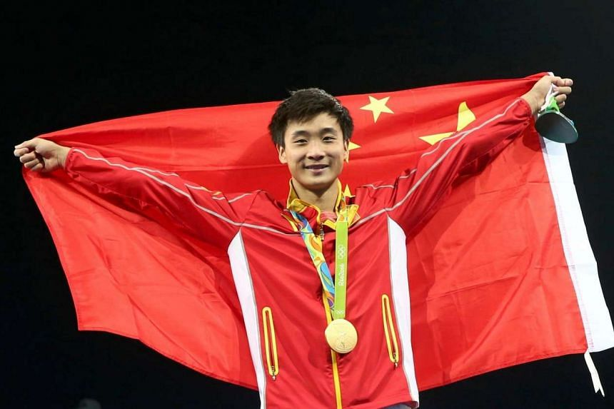 Cao Yuan of China celebrates winning the gold with his national flag at the men's 3m springboard victory ceremony on August 16.