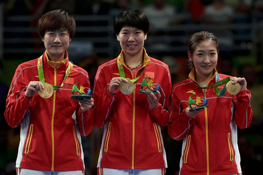 Gold medallists Li Xiaoxia, Liu Shiwen and Ding Ning of China pose on the podium on August 16.