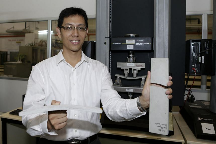 Prof Yang En-Hua, showing the effect of applying pressure using the four point bending machine (behind).