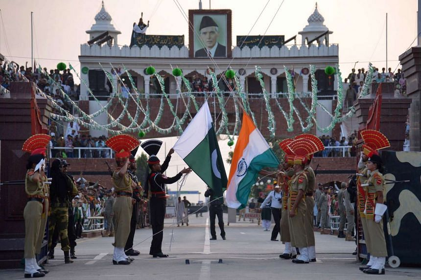 Pakistani Rangers (in black) and Indian Border Security Force personnel (in brown) perform the flag off ceremony at the India Pakistan Wagah Border Post on Aug 14, 2016.