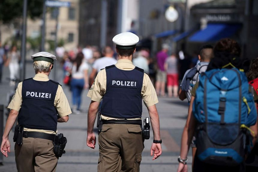 Policemen patrol through a pedestrian area in Munich, southern Germany, on July 23, 2016, one day after the attack at the shopping centre in Munich.