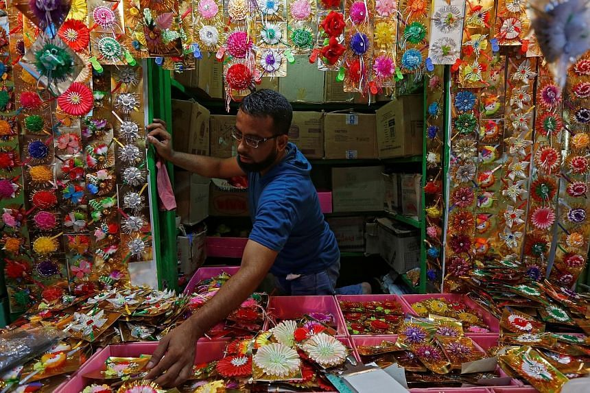 """A man arranging """"rakhis"""" or sacred threads yesterday as he waits for customers at his roadside stall in Kolkata, India, ahead of the Hindu festival Raksha Bandhan tomorrow. During the festival celebrating the bond between brothers and sisters, a woma"""