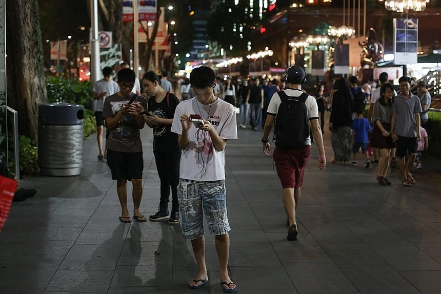 People playing Pokemon Go in Orchard Road. The smartphone app, which was launched in Singapore earlier this month, was cited in Parliament yesterday as an example of new ways of consuming content.