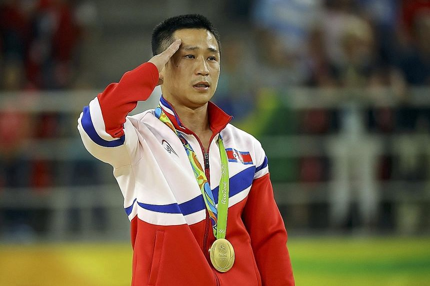 North Korea's Ri Se Gwang salutes as his country's national anthem is played during the medal ceremony. The 31-year-old crushed his vault rivals with the hardest combination of two jumps to add Olympic gold to his two world titles in 2014 and 2015.