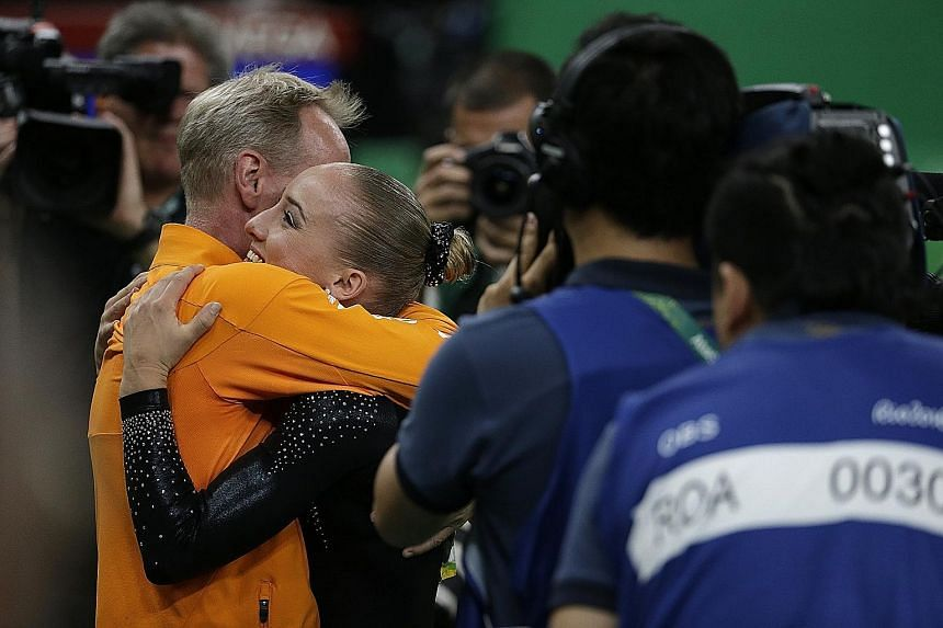 Above: Sanne Wevers of the Netherlands hugging her coach and father Vincent after receiving her gold-winning score in the balance beam final.