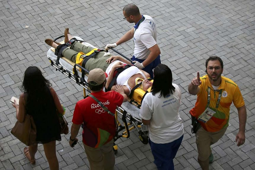 A woman is transported to an ambulance after being hit by the overhead television camera.