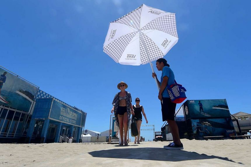 A man uses an umbrella to provide some relief from hot weather at Huntington Beach, California on July 22, 2016.