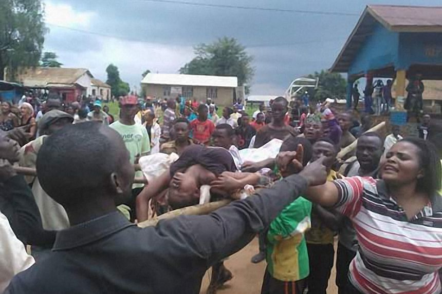 People argue as a woman is transported to the local hospital in Beni on Aug 15, 2016 during scenes of tension following a wave of unrest and violence in the region.