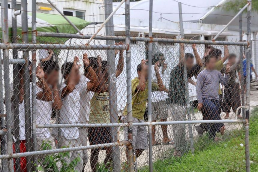Asylum seekers look at the media from behind a fence at the Manus Island detention centre on March 21, 2014.