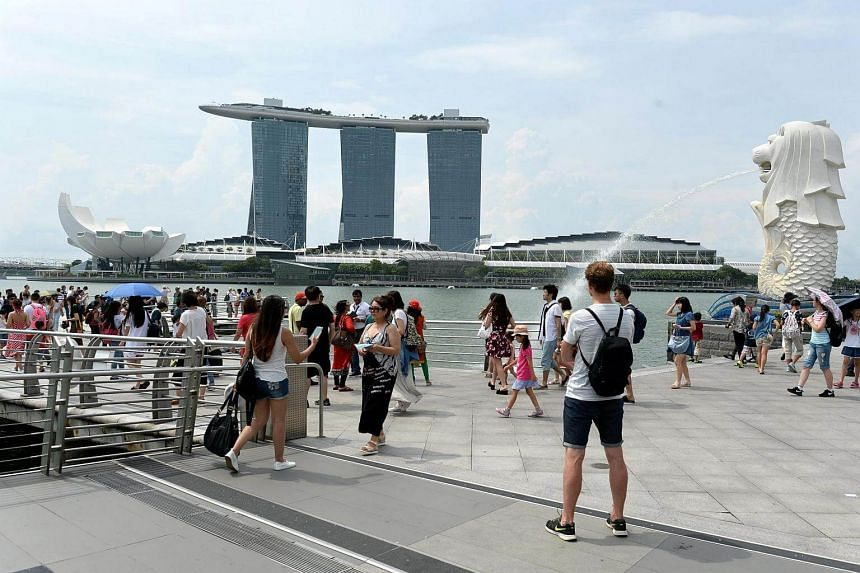 Tourists gather at Merlion park to take pictures overlooking Marina bay in Singapore on August 11.