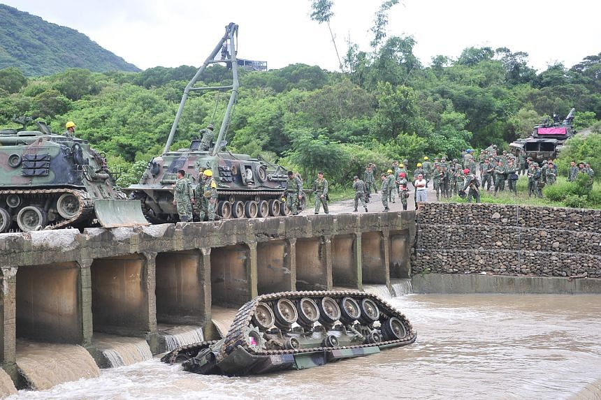 The CM11 armoured vehicle carrying five soldiers was returning to camp in southern Pingtung county when it slipped from a bridge and fell upside down into the Wangsha River, the army said.