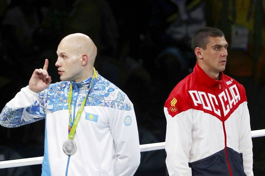 Silver medallist Vassiliy Levit of Kazakhstan gesturing for the crowd to remain silent while Russia's national anthem played for Evgeny Tishchenko, winner of the boxing heavyweight gold on a contentious decision.