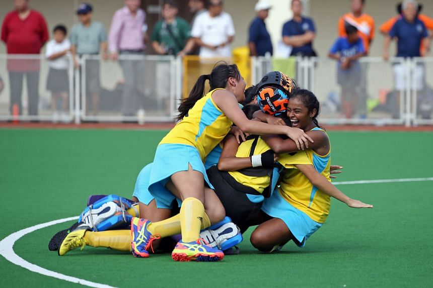 Shaalini Subramaniam of Crescent Girls' School (extreme right) is mobbed by her exuberant team-mates yesterday after scoring the penalty stroke that clinched their first C Division crown since 1994.