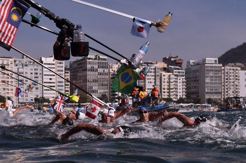 Swimmers racing past the feeding sticks in the waters off Fort Copacabana during the 10km open-water marathon.