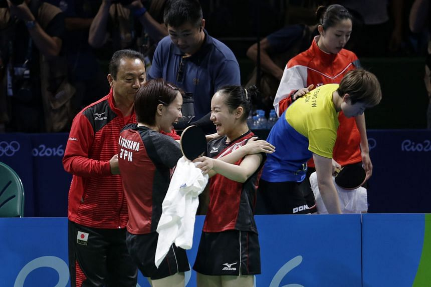 Singapore's Yu Mengyu consoling Feng Tianwei (right), while Kasumi Ishikawa (left) and Mima Ito celebrate the latter's victory over Feng, which gave Japan the winning point in their 3-1 victory over Singapore, and the team bronze.