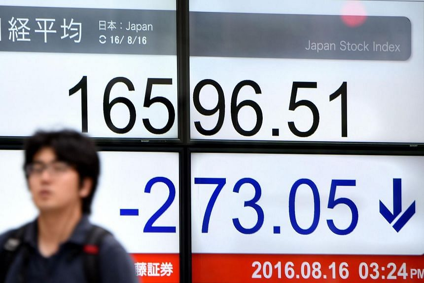 A man walks past an electric quotation board flashing the Nikkei key index of the Tokyo Stock Exchange in Tokyo on August 16.