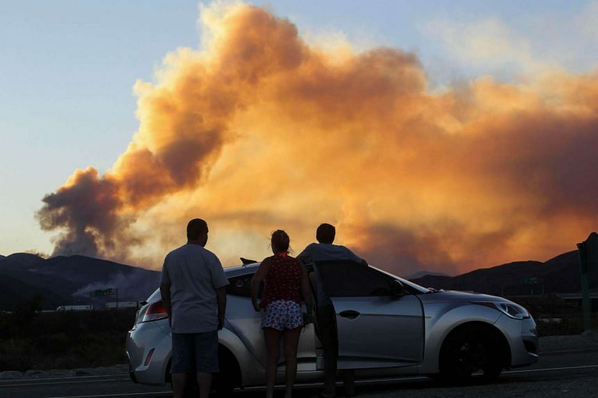 People watch the so-called Blue Cut wildfire in Lytle Creek, California on August 16.