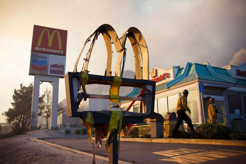 A melted sign from a McDonald's restaurant shows the damage as firefighters check the area after a wildfire swept through Cajon Junction, California, USA on August 16.