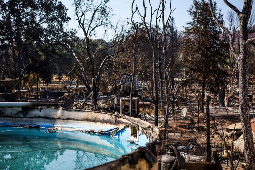 Burned residences, vehicles and a pool line a fire-ravaged neighborhood after the Clayton Fire burned through Lower Lake, California, on August 16.