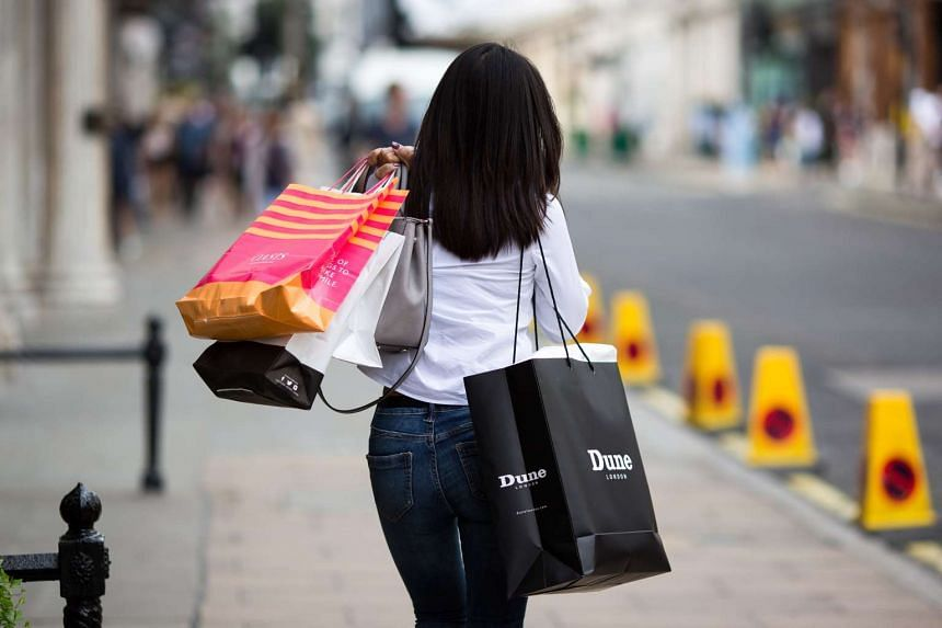 A pedestrian carries shopping bags on Bond Street in London on Aug 8, 2016.