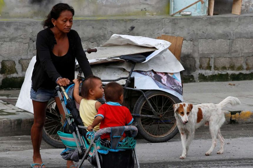 A woman pushes her children on a stroller after around a dozen homeless people were evicted along a road in Makati, Metro Manila, Philippines on Aug 18, 2016.