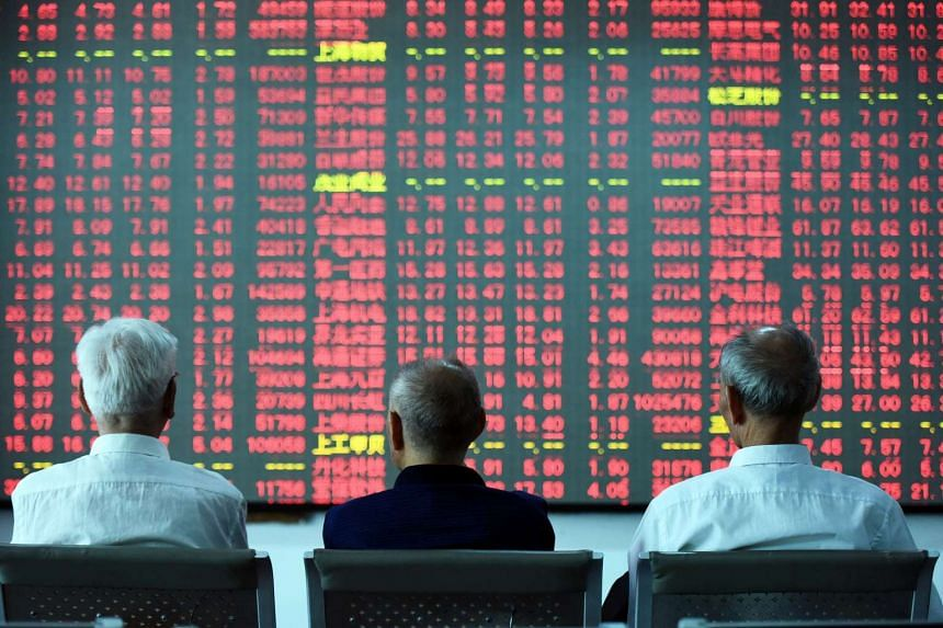 Chinese investors sit in front of a screen showing stock market movements at a securities firm in Hangzhou, eastern China's Zhejiang province on May 31.