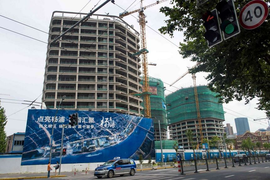 Cars pass by a housing construction site in Shanghai on July 1, 2016.