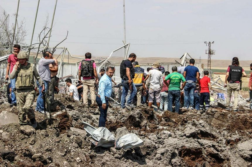 Turkish police officers and rescue personnel search the site of a car bomb explosion on Aug 15, 2016 in Diyardakir, Turkey.