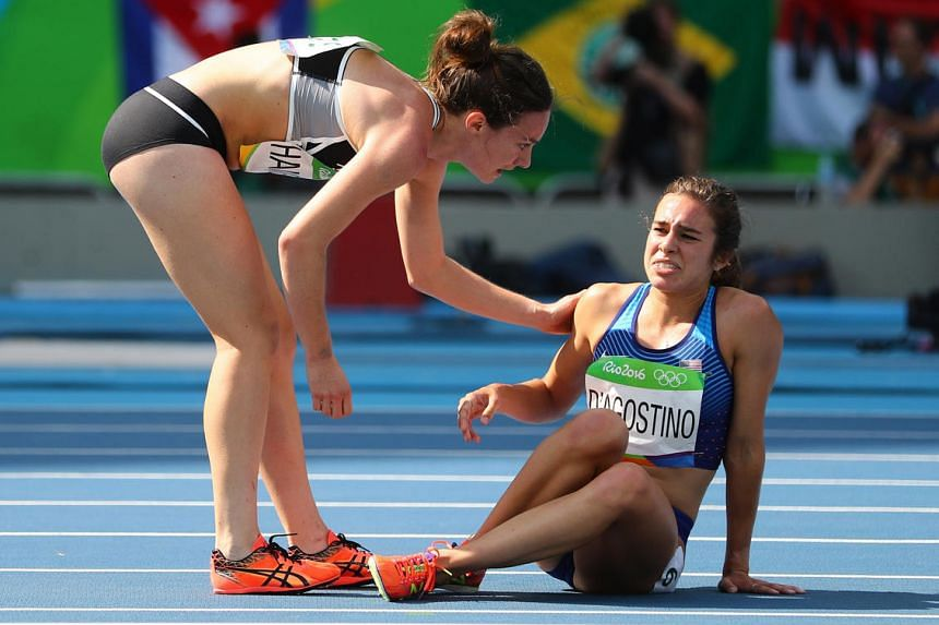 Nikki Hamblin of New Zealand stops running during the race to help fellow competitor Abbey D'Agostino of USA after D'Agostino suffered a cramp on August 16.