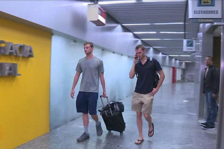 US swimmers Jack Conger (left) and Gunnar Bentz walk into a police office of Rio de Janeiro's international airport after they were stopped from boarding a flight to the United States following their participation in the Rio 2016 Olympic Games on Aug