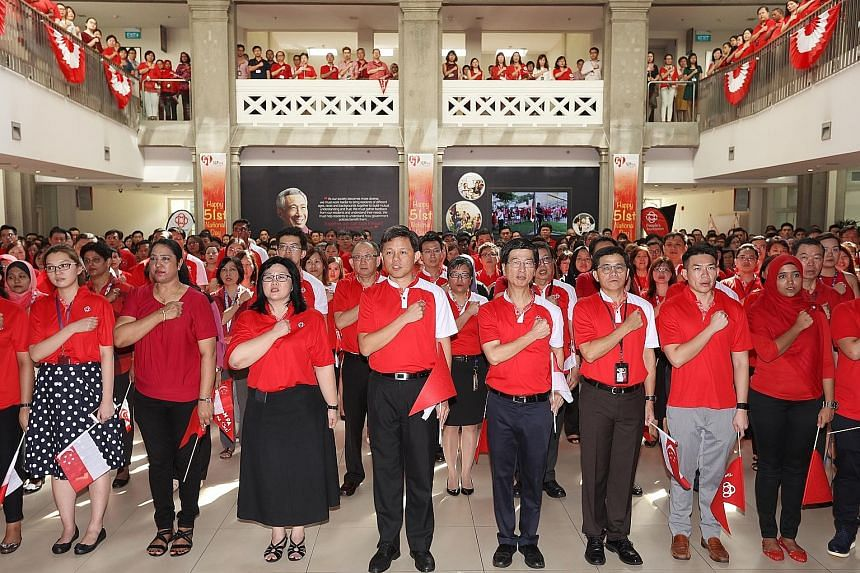 Mr Chan (centre) and People's Association chief executive director Ang Hak Seng (next to Mr Chan) reciting the pledge with some 500 PA staff during a National Day observance ceremony yesterday. The minister said terrorism is not the only threat to un