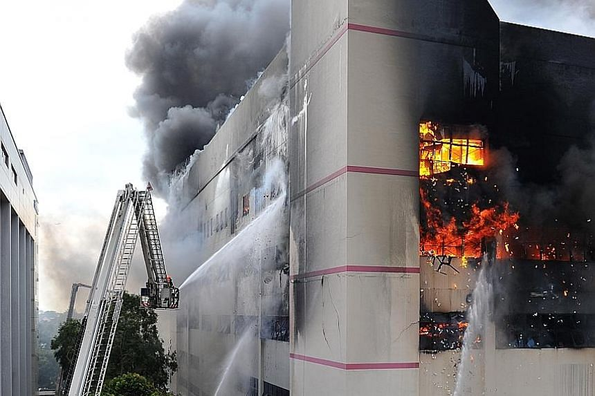 Firefighters using water jets to fight the raging flames from the outside of CK Building. The fire was brought under control after about five hours, but it had yet to be put out at press time. A column of smoke rising from CK Building in Tampines Str
