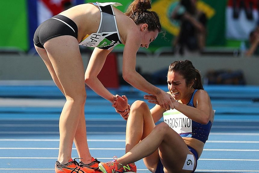 Nikki Hamblin of New Zealand (left) stops running to offer encouragement to injured Abbey D'Agostino of the United States, after the duo had accidentally collided during an earlier part of their women's 5,000m race.
