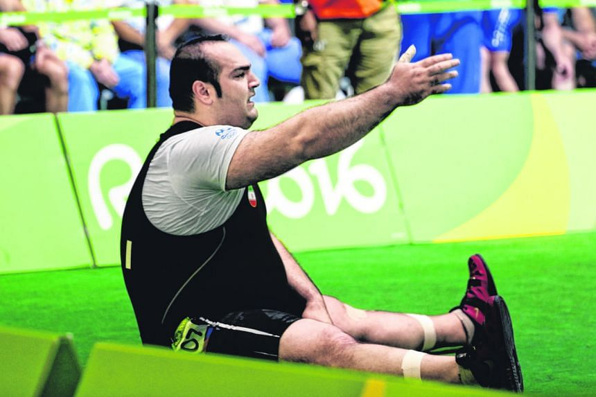 Georgia's Lasha Talakhadze roars as he attempts a lift during the over-105kg competition, which he won gold with a world-record total of 473kg. Iran's Behdad Salimikordasiabi, the defending champion, sits in dejection after failing to register a lift