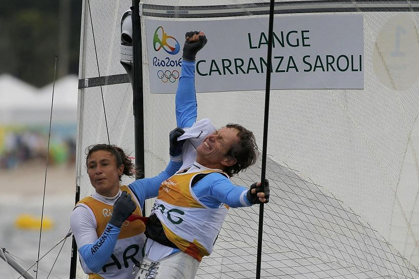 Argentinians Santiago Lange and Cecilia Carranza Saroli celebrating their mixed multi-hull Nacra 17 success. One of Latin America's most legendary sailors, Lange lost a lung to cancer a year ago but bounced back to win his first-ever gold in his sixt