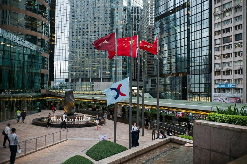 Staff of Hong Kong Exchanges and Clearing Limited lowering its flag in Hong Kong. China's central government has approved plans to link trading between the Shenzhen stock exchange and the Hong Kong market, paving the way for a long-awaited reform.