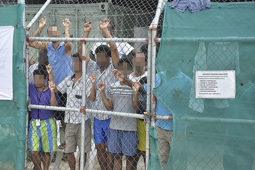 A 2014 file picture showing asylum-seekers behind a fence at the Manus Island detention centre in Papua New Guinea. The camp was in the spotlight this week after Australian media published graphic images of two Afghan men there who had allegedly been