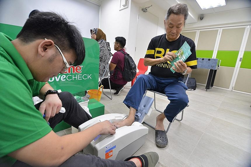 Mr Tan See Ching, 69, undergoing a scan to check his bone density and strength yesterday morning at the Lions Befrienders Bendemeer Senior Activity Centre. He is one of the 60 underprivileged seniors from the centre who were given the scan during a c