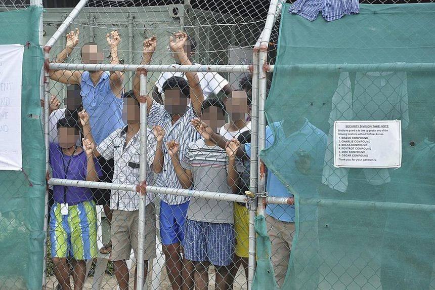 Asylum seekers behind a fence at the Manus Island detention center, in Papua New Guinea in 2014.
