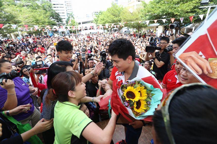 Joseph Schooling receiving flowers from fans.