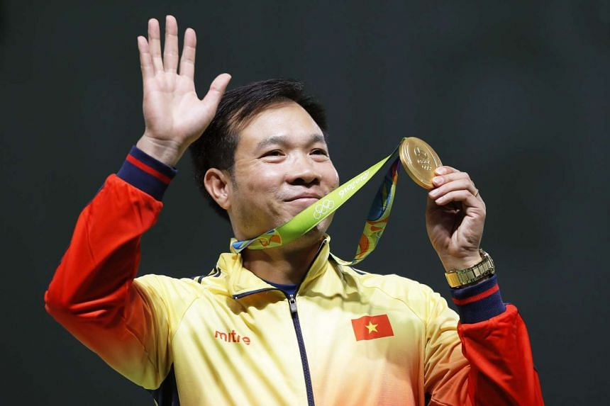 Hoang Xuan Vinh of Vietnam celebrates with his gold medal on the podium after winning the men's 10m Air Pistol final of the Rio 2016 Olympic Games on Aug 6, 2016.