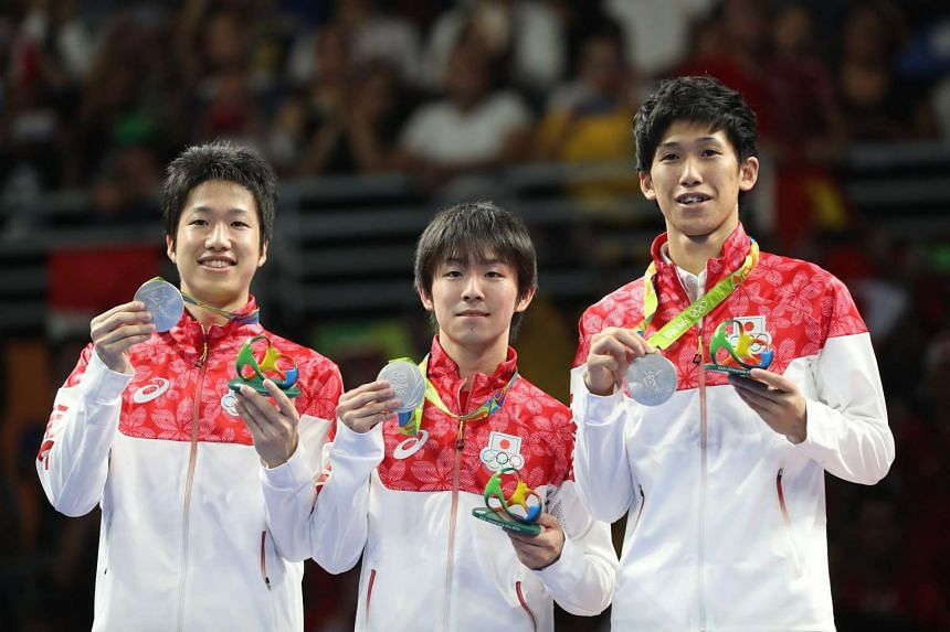 Japan's Jun Mizutani, Koki Niwa and Maharu Yoshimura hold up their table tennis team silver medals during the awards ceremony in the men's Team match of the Rio 2016 Olympic Games on Aug 17, 2016.